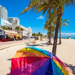 Hollywood Beach, Florida - July 6, 2017: The promenade along the beach lined with palm trees and resorts is a popular tourist destination in Broward County.